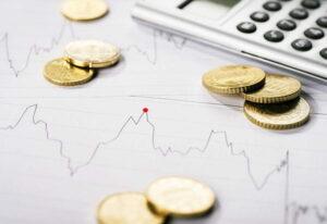 Diagramm zeigt den Verlauf eines Kurses und ist umgeben von Münzen und einem Taschenrechner.